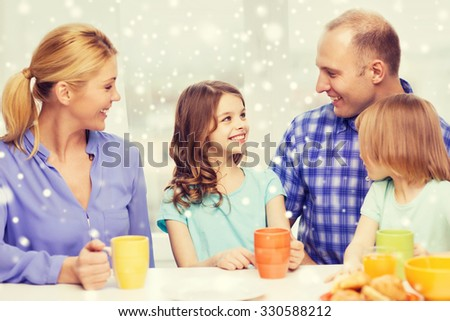 food, family, children, happiness and people concept - happy family with two kids having breakfast at home