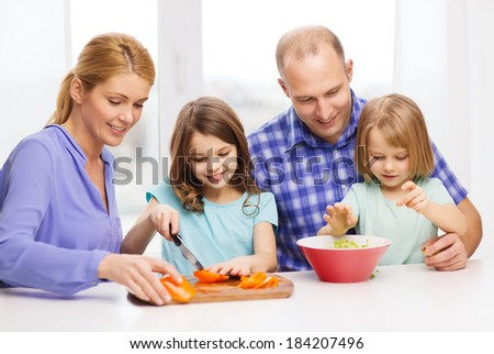 food, family, children, happiness and people concept - happy family with two kids making dinner at home - stock photo