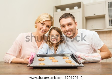 food, family, christmas, hapiness and people concept - happy family in making cookies at home - stock photo