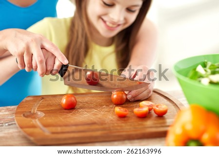 food, family, cooking and people concept - close up of happy girl and mother making dinner and chopping cherry tomatoes on cutting board with knife in kitchen - stock photo