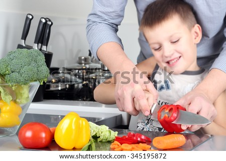 food, family, cooking and people concept - Man chopping paprika on cutting board with knife in kitchen with son - stock photo