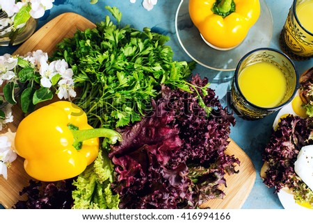 Food, food styling, cooking. Fresh yellow bell peppers, lettuce, parsley and orange juice - stock photo