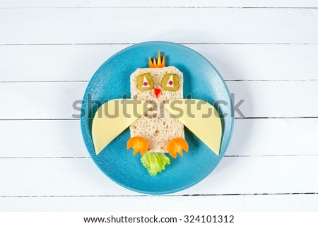 Food for kids: funny sandwich on blue plate on white background - stock photo