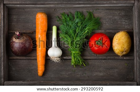 Food for raw foodists. Set of different fresh raw vegetables in an old wooden box: garlic, tomato, carrot,  potatoes, beets,  dill. Harvest. Ingredients for vegetable dishes - stock photo
