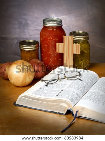 FOOD FOR THOUGHT - canned vegetables and fruit with a bible and pair of glassed on a kitchen counter - stock photo
