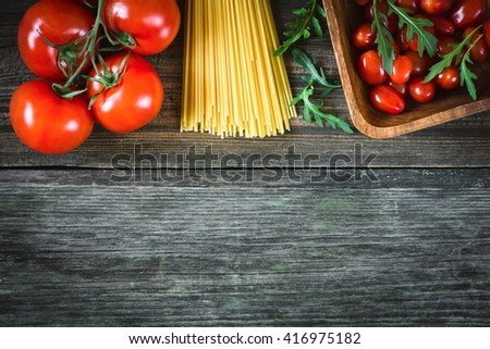 Food frame: pasta cooking ingredients, dry pasta, tomatoes, arugula on wooden background. Top view, copy space