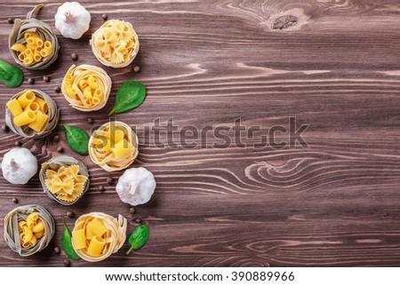 Food frame. Pasta ingredients on dark grunge backdrop, copy space - stock photo