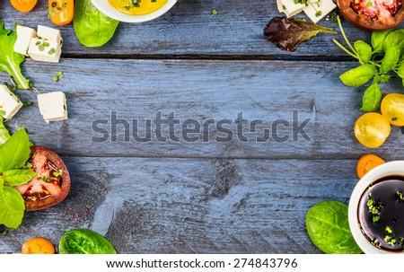 Food frame with salad ingredients: oil,vinegar, tomatoes, basil and cheese on blue rustic wooden background, top view, horizontal - stock photo