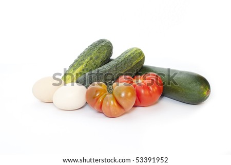 Food from the garden: eggs, cucumber, courgettes and tomatoes - stock photo