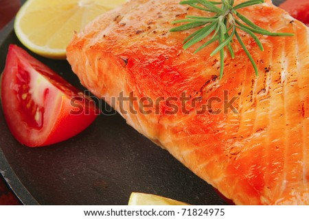 food: grilled salmon on iron pan over wooden plate isolated on white background - stock photo