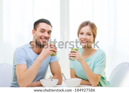 food, home, couple and happiness concept - smiling couple having breakfast at home - stock photo