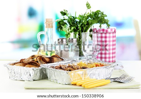 Food in boxes of foil on tablecloth on window background