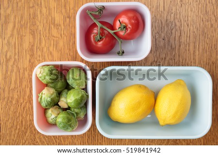 Food in containers including tomatoes, lemons and Brussels Sprouts.