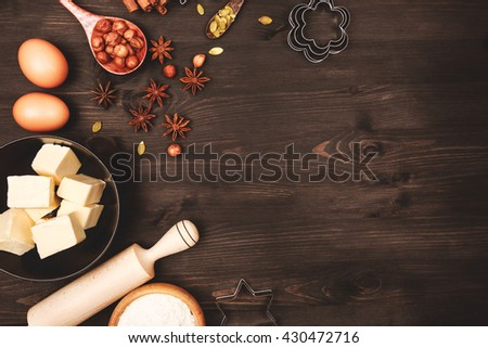 Food ingredients and kitchen utensils for cooking gingerbread or cookies on dark wooden background. Place for text. - stock photo