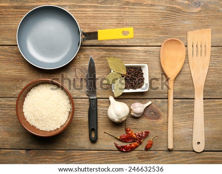 Food ingredients and kitchen utensils for cooking on wooden background - stock photo