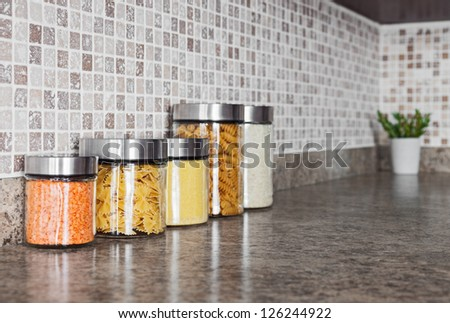 Food ingredients in glass jars on a kitchen counter top. - stock photo