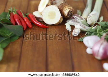 food ingredients of lemon grass soup (spicy Thai soup  or Tom Yam) include galangal, lime leaves, lime, lemon grass and red chili on wooden background.