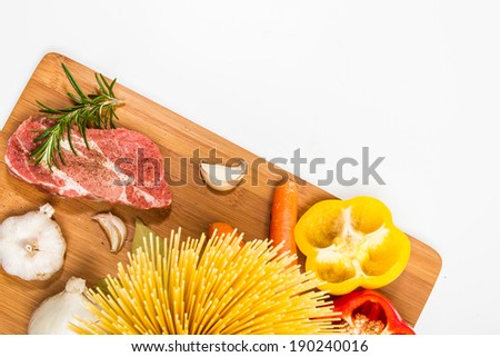 Food ingredients scattered around the wooden cutting board. - stock photo