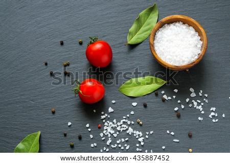Food ingredients: tomatoes, bay laurel leaves and salt on black slate stone . Top flat view - stock photo