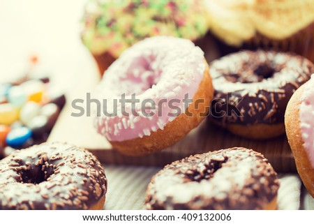 food, junk-food and eating concept - close up of glazed donuts on table - stock photo