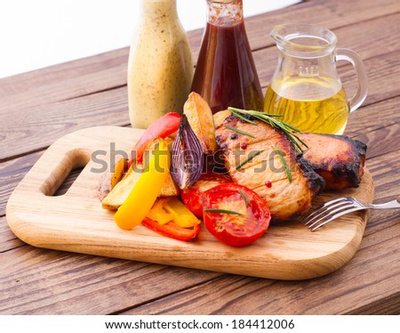Food. Meat barbecue with vegetables on wooden surface. Meat steak. Beef steak bbq. Tomatoes, peppers, spices for cooking meat. - stock photo