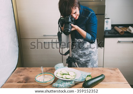 Food photographer taking still life pictures in the kitchen - stock photo