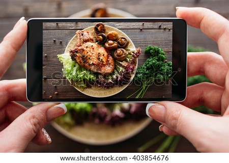 Food photography of baked pork with fresh vegetables. Home made food photo for social networks. Top view mobile phone photo of baked meat.  - stock photo