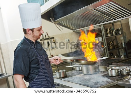 Food preparation. Chef cook in restaurant kitchen with pan over stove doing flambe  - stock photo