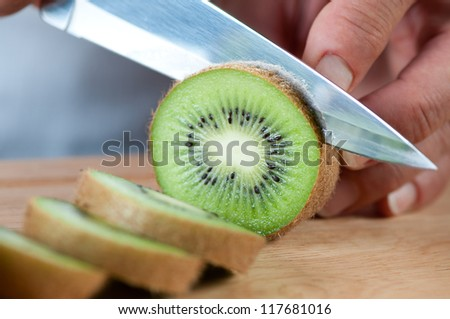 Food preparation � cutting a kiwi fruit, studio shot - stock photo