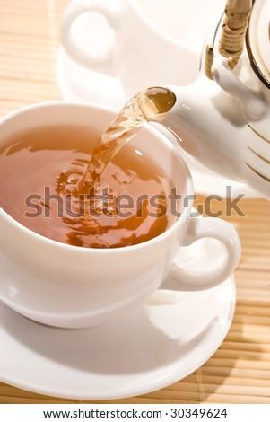 food series: flowing golden tea into cup - stock photo