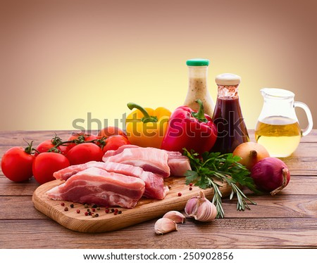 Food. Sliced pieces of raw meat for barbecue with fresh vegetables and mushrooms on wooden surface. Meat raw steak. Beef steak bbq. Tomatoes, peppers, spices for cooking meat. - stock photo