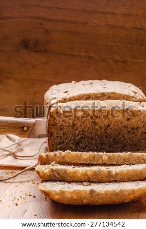 Food. Sliced whole wheat bread and knife on cutting board wooden background - stock photo