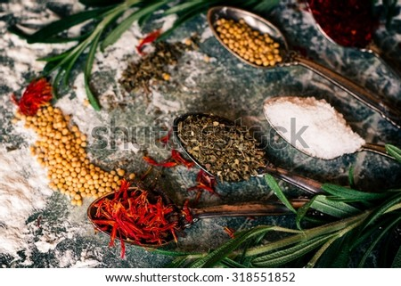 Food spice seasoning ingredients for cooking in cuisine on dark background. Dry powder curry, ginger, cardamon, rosemary, salt, saffron, paprika. Asian red, yellow, green colorful aroma condiment.   - stock photo
