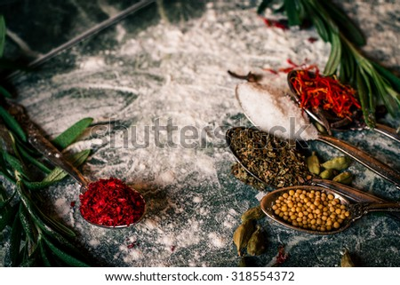 Food spice seasoning ingredients for cooking in cuisine on dark background. Dry powder curry, ginger, cardamon, rosemary, salt, paprika, saffron. Asian  yellow, green colorful aroma condiment.   - stock photo