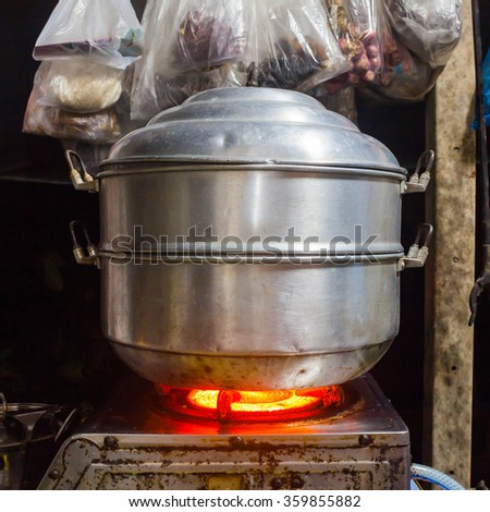 Food steamer pot  on stove kiTchen outdoor in thailand,night - stock photo