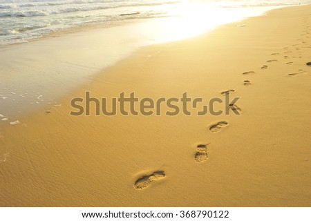 Food steps on the beach with the effect of morning sun light on the sand and the wave. - stock photo