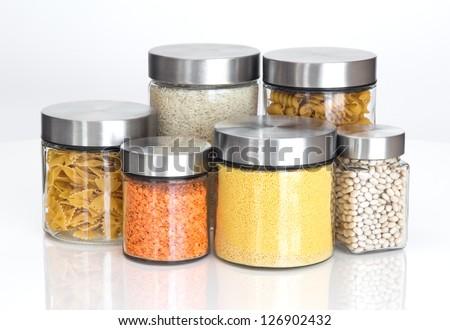 Food storage. Food ingredients in glass jars, on white background. - stock photo