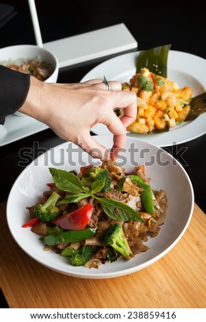 Food stylist grooms a dish by adding sweet basil garnish to the traditional thai dish Pad Kee Mao drunken noodle. - stock photo