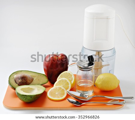 food tray with avocado,apple,lemon,spoons and a blender