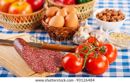 foods (tomatoes, eggs, apples, Bulgarian pepper, hazelnuts, garlic and smoked sausage on cutting board with knife) on blue and white checkered tablecloth