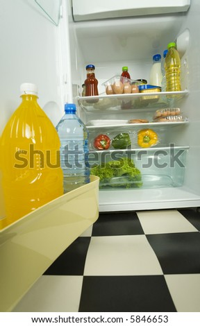 Foodstuffs in opened fridge. Front view. - stock photo