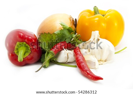Foodstuffs on white including peppers, coriander, chilli, garlic and onion - stock photo