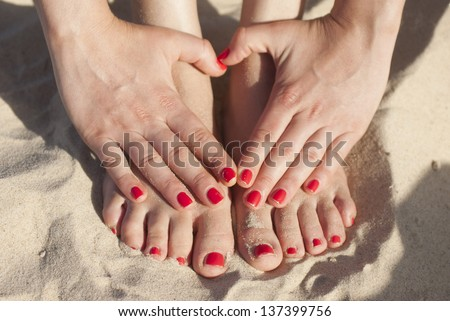 Foot and hands on the sand with red nails - stock photo