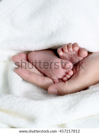 foot child in a hand of an adult
