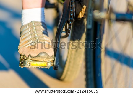 foot girl in sneakers on a bicycle pedal - stock photo