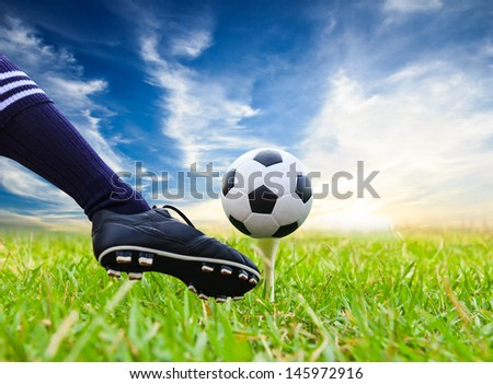 foot kicking soccer ball on golf tee - stock photo