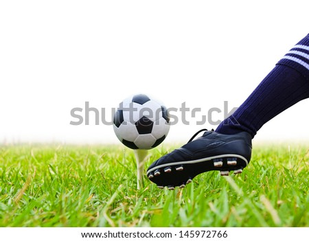 foot kicking soccer ball on golf tee isolated - stock photo