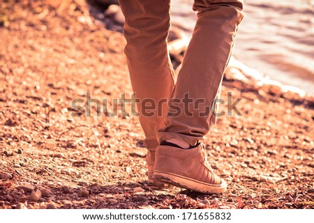 Foot man walking outdoor on beach trendy style melancholy concept - stock photo