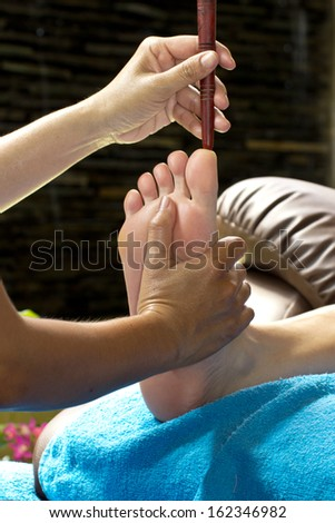foot massage by wood stick for frontal sinuses  - stock photo