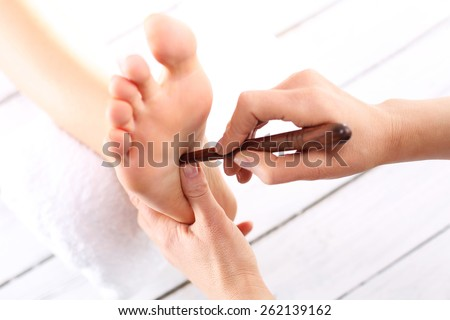 Foot massage, Foot reflexology.Natural medicine, reflexology, acupressure foot massage oppresses energy flow points - stock photo